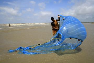 Indian fisherwoman adjusts her fishing net against the backdrop of monsoon rain clouds at Mandarmoni