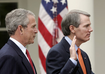Rob Portman raises his hand during his swearing in ceremony at the White House in Washington