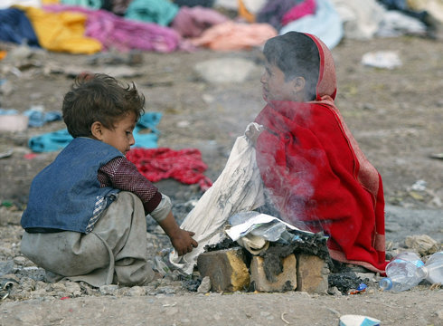 Children who survived the earthquake light a fire in front of their collapsed house in Balakot