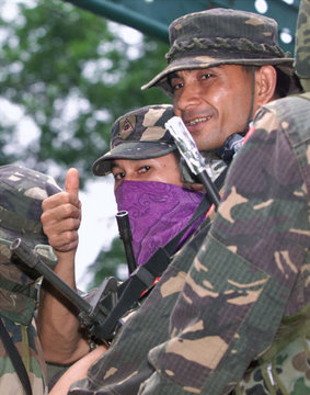 A MASKED FILIPINO SOLDIER GIVES A THUMBS UP SIGN IN JOLO.
