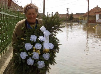 LOCAL RESIDENTS OF FLOODED VILLAGE CARRY WREATH.