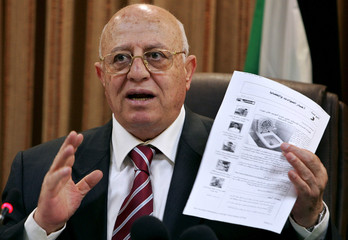 Outgoing Palestinian Prime Minister Ahmed Qurie displays a printout from a website as an example of cartoons offensive to the Muslim world during a cabinet meeting in Ramallah