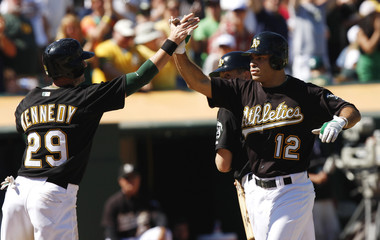 Oakland Athletics' Hairston is congratulated by teammate Kennedy following grand slam home run against the Seattle Mariners during MLB baseball game in Oakland
