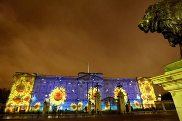 An image showing yellow sunflowers and falling snowflakes is projected onto Buckingham Palace in Lon..