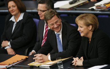 German Chancellor Merkel and Foreign Minister Westerwelle smile during session at the Bundestag in Berlin