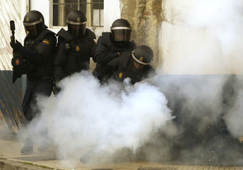 Spanish riot police take cover as a homemade rocket explodes during clashes in Gijon, northern Spain.