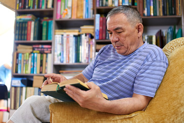 An adult Kazakh reads a book sitting in his home library