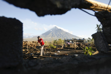 Nestor Barce collects wood as he is pictured, framed in the ruins of a house against Mount Mayon, an active volcano, in the background after Typhoon Durian in Albay province, south of Manila