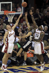 San Antonio Spurs Parker puts up a shot between Cleveland Cavaliers Pavlovic and James during their NBA basketball game in Cleveland