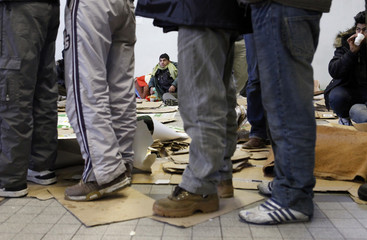 Asylum seekers wait for food distribution after they slept in gymnasium converted into shelter in northern France