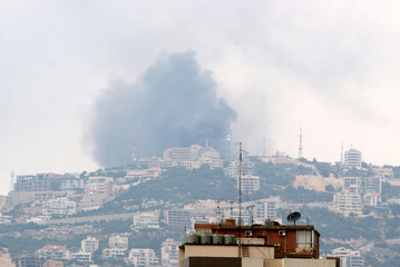 Smoke rises from where mobile telephone and television towers stood following Israeli air strikes in Fatka