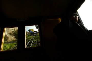 MAN LOOKS OUT OF WINDOW OF FUNICULAR RAILWAY IN VALPARAISO.
