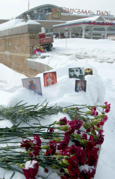 FLOWERS AND PAPER ICONS LAY IN SNOW OUTSIDE A WATER PARK IN MOSCOW.