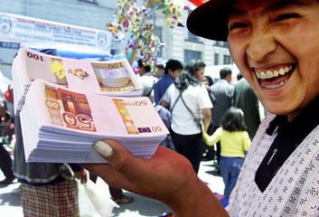 """An Aymara Indian woman holds fake Euro bills, the European Union's new currency, for sale in the """"Al.."""
