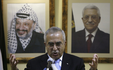 Palestinian Prime Minister Fayyad gestures during news conference in Ramallah