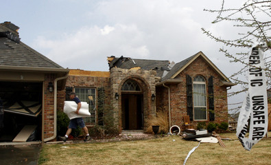 A restoration company worker removes items from a home damaged after a suspected tornado and heavy storms hit Edmond