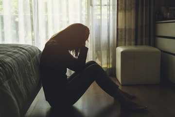 depressed woman sitting in the dark bedroom
