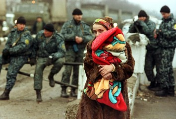 A CHECHEN REFUGEE WOMAN HOLDS HER BABY RETURNING HOME TO CHECHNYA.