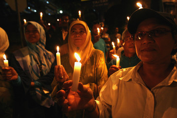 Supporters of Malaysia's opposition figure Anwar Ibrahim hold candlelight gathering outside police headquarters in Kuala Lumpur