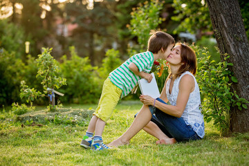 Young beautiful mother, sitting in a garden, little boy, her son, bringing gerbera flowers and present