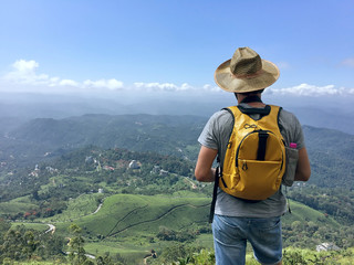 Young caucasian male traveling backpacker up hill and down dale in Munnar, Kerala state, Idukki district, India