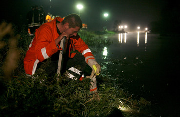 A Firefighter checks the water level at a dike against the floods of the river Innerste in Heersum near the northern German town of Hanover