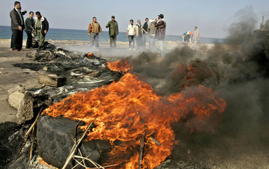Palestinians stand next to burning tyres after Palestinian [policemen] closed the roads to protest a..