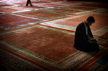 IRANIAN RELIGOUS STUDENT READS BOOK BEFORE PRAYERS IN SEMINARY IN TEHRAN.