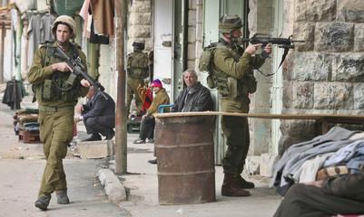 Israeli soldiers patrol the market in Hebron
