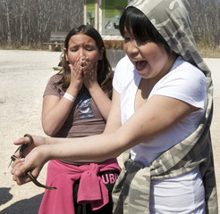 Students reacts to a Red-sided garter snake outside its winter den in Narcisse
