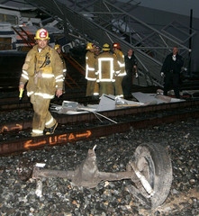 Firefighter walks past axle of car involved in Metrolink train collision and derailment.