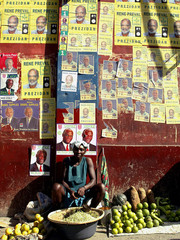 Haitian woman sells fruits in front of wall decorated with banners of Haiti's presidential candidates in Port-au-Prince