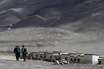 Yak herders walk towards their dwellings as they prepare their herd at the foot of Mount Everest in the Tibet Autonomous
