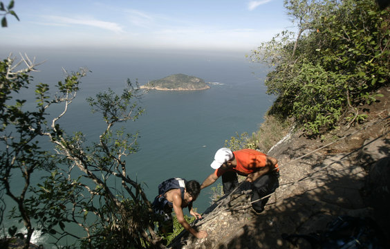 Brazilian rock climber Fred Moura helps another climber at the landmark Sugar Loaf mountain in Rio de Janeiro