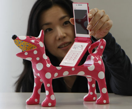 An employee of Japanese mobile phone carrier KDDI poses as she displays the company's new polka dot pattern mobile phone and dog-shaped phone holder designed by Japanese artist Yayoi Kusama in Tokyo