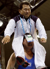 South Korea's Kim Gwang-seok carries team official Park Myung-suk on his shoulders after winning men's Greco-Roman 120kg gold medal match at 15th Asian Games in Doha