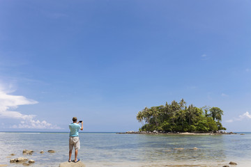 tourist man standing on the stone in summer season and take a photo beautiful small island in phuket thailand.