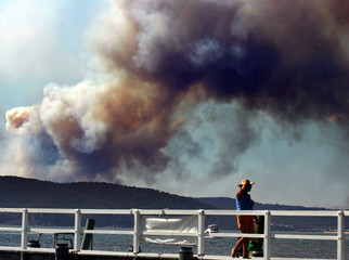 Woman walks along wharf in northern Sydney suburb of Palm Beach as smoke from fire on Central Coast can be seen in sky behind