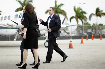 Republican presidential candidate Huckabee walks to board his plane at Miami International airport