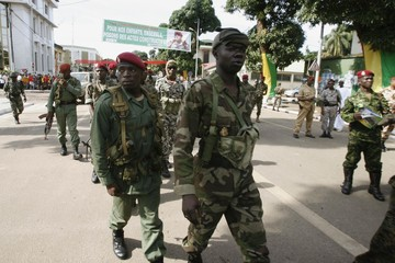 Guinean soldiers walk along a street in Conakry
