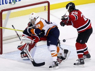 New York Islanders Comrie crashes into New Jersey Devils Brodeur in NHL action in Newark