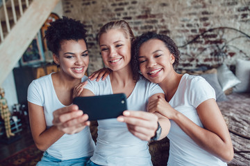 Pretty girls having fun and make selfie sitting near the bed. Two afro-americans and one european girl.