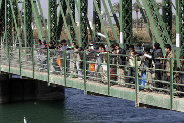 Students throw plastic bottles containing peace messages off bridge into Euphrates river in Falluja