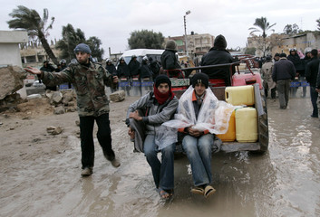 Palestinians return to Gaza through a destroyed section of the border wall between Gaza and Egypt