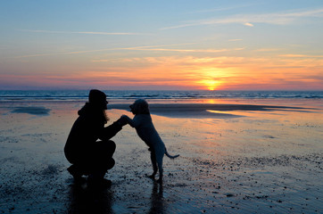 Frau mit Hund vor Sonnenuntergang