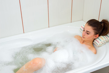 young girl lies in hot water in the bath with foam