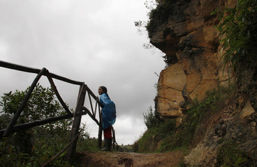 A woman looks at sarcophaguses from the Chachapoyas culture at the valley of Luya in Chachapoyas