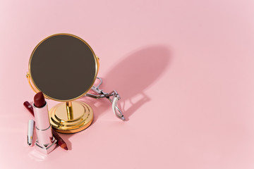 make up products and tools on pink background