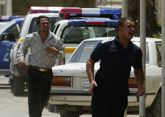 Men cry as they rush to a hospital to look for their relatives who were on a minibus that as hit by a bomb in Baghdad
