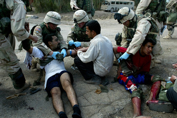 INJURED IRAQI BOY AND HIS UNCLE RECEIVE MEDICAL ATTENTION FROM USSOLDIERS IN TAJI.